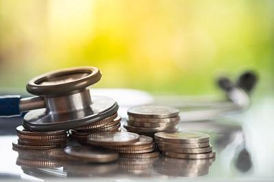 Ein Stethoskop liegt auf mehreren Münzen.