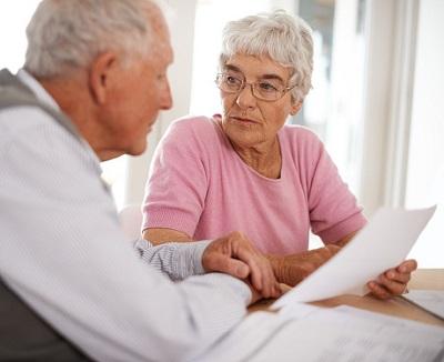 Senior mit Frau am Tisch und Papieren