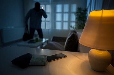 Einbrecher mit Handy, Geld und Lampe auf Tisch