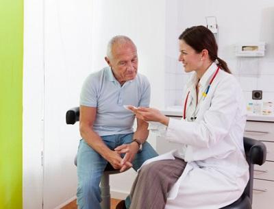 Ärztin mit älterem Patienten im Behandlungszimmer