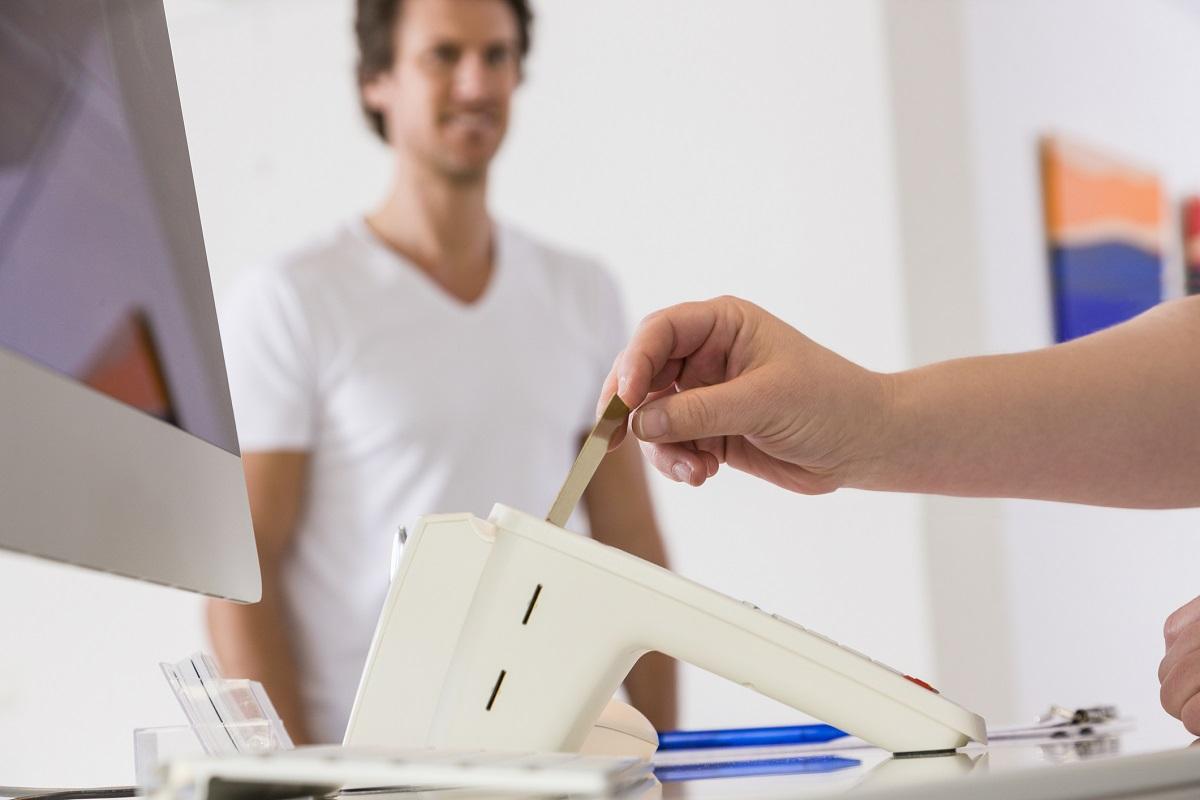 Patient lässt seine Gesundheitskarte beim Arzt einlesen.