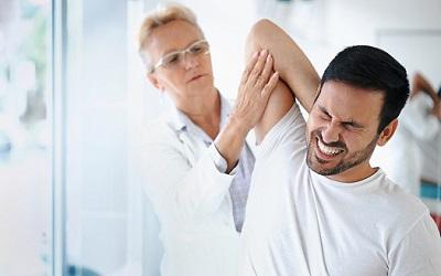 Eine Ärztin behandelt einen Patienten wegen Rückenschmerzen.