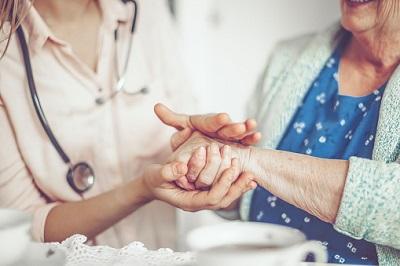Pflegerin und Seniorin halten Hände.