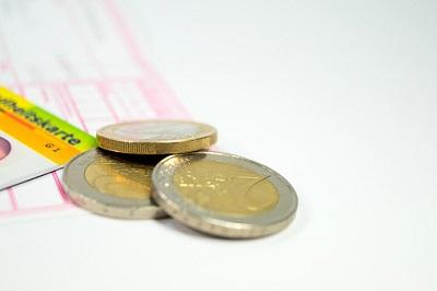 Versichertenkarte mit Euro-Münzen