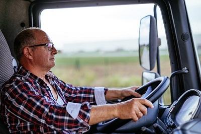 Älterer Lkw-Fahrer sitzt am Steuer seines Lkws.