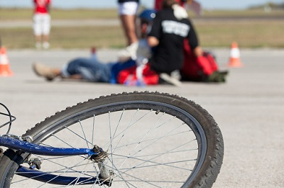Rad mit Unfallopfer und Notarzt im Hintergrund