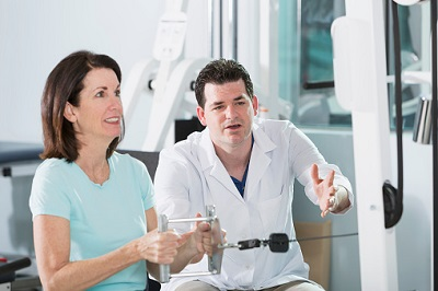 Ältere Patientin macht Kraftübung zusammen mit Physiotherapeut.