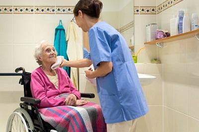 Ältere Frau im Rollstuhl mit Altenpflegerin im Bad
