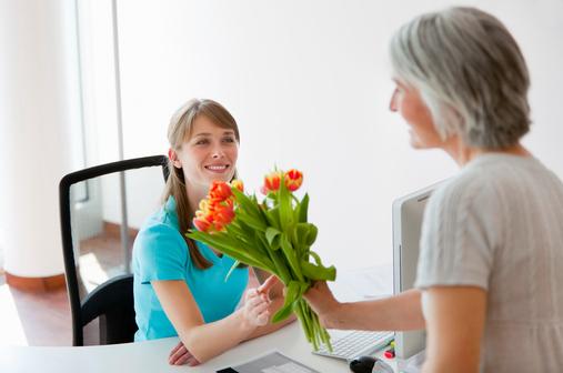 Patientin schenkt Arzthelferin einen Blumenstrauß