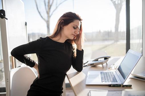 Eine junge Frau sitzt erschöpft vor ihrem Laptop am Schreibtisch.