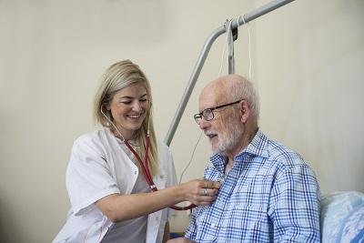 Pflegerin horcht mit Stethoskop älteren Mann ab.