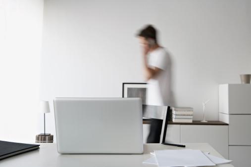 Mann telefoniert im Büro, Schreibtisch mit Laptop steht im Vordergrund.