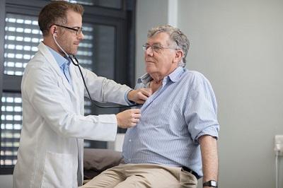 Arzt untersucht älteren Patienten mit Stethoskop