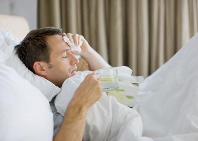 Mann liegt krank im Bett mit einem heißen Getränk