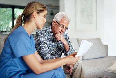 Pflegerin sieht Papiere mit älterem Mann im Wohnzimmer durch