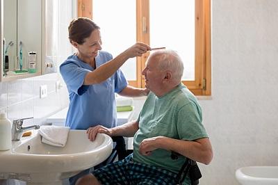 Altenpflegerin kämmt Heimbewohner die Haare.