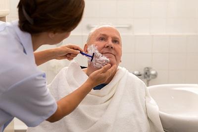 Pflegerin rasiert einen Heimbewohner.