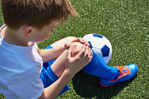 Junge mit aufgeschürftem Knie sitzt mit einem Fußball auf dem Rasen.