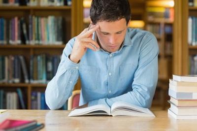 Ein Student sitzt in einer Bibliothek und liest.