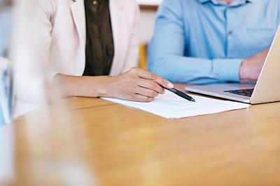 Eine Frau und ein Mann sitzen am Laptop und haben ein Dokument vor sich liegen.