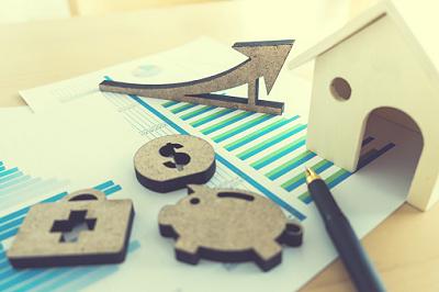 Kleine Sparsymbole und ein Holzhaus liegen auf ausgedruckten Statistiken