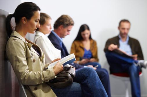 Patienten sitzen im Wartezimmer einer Arztpraxis.