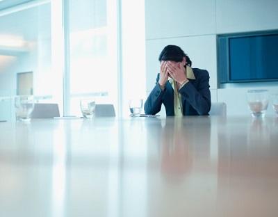 Angestellte sitzt frustriert in einem Konferenzraum.