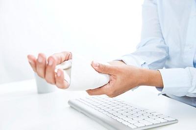 Hand in Verband und Tastatur