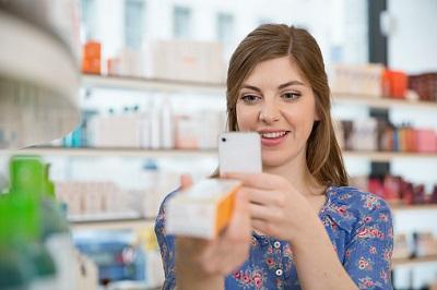 Frau fotografiert Medikament mit Smartphone in einer Apotheke.