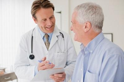Arzt spricht mit einem älteren Patienten.