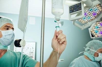 Arzt überprüft Infusion im OP.