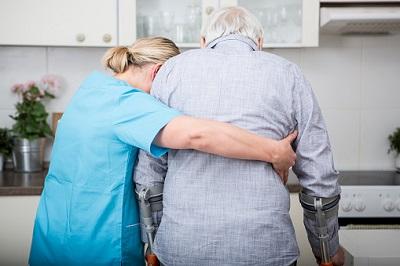 Eine Krankenschwester hilft einem Senior auf Krücken.