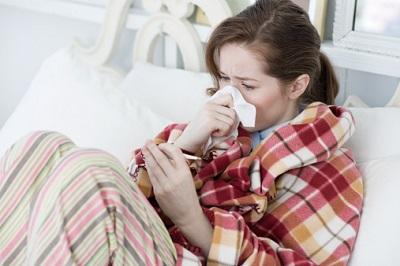 Eine Frau liegt krank im Bett und überprüft ihre Temperatur.