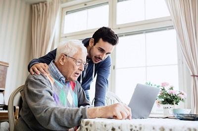 Senior mit Enkel vor Computer