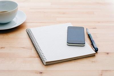 Handy und Schreibblock auf Tisch