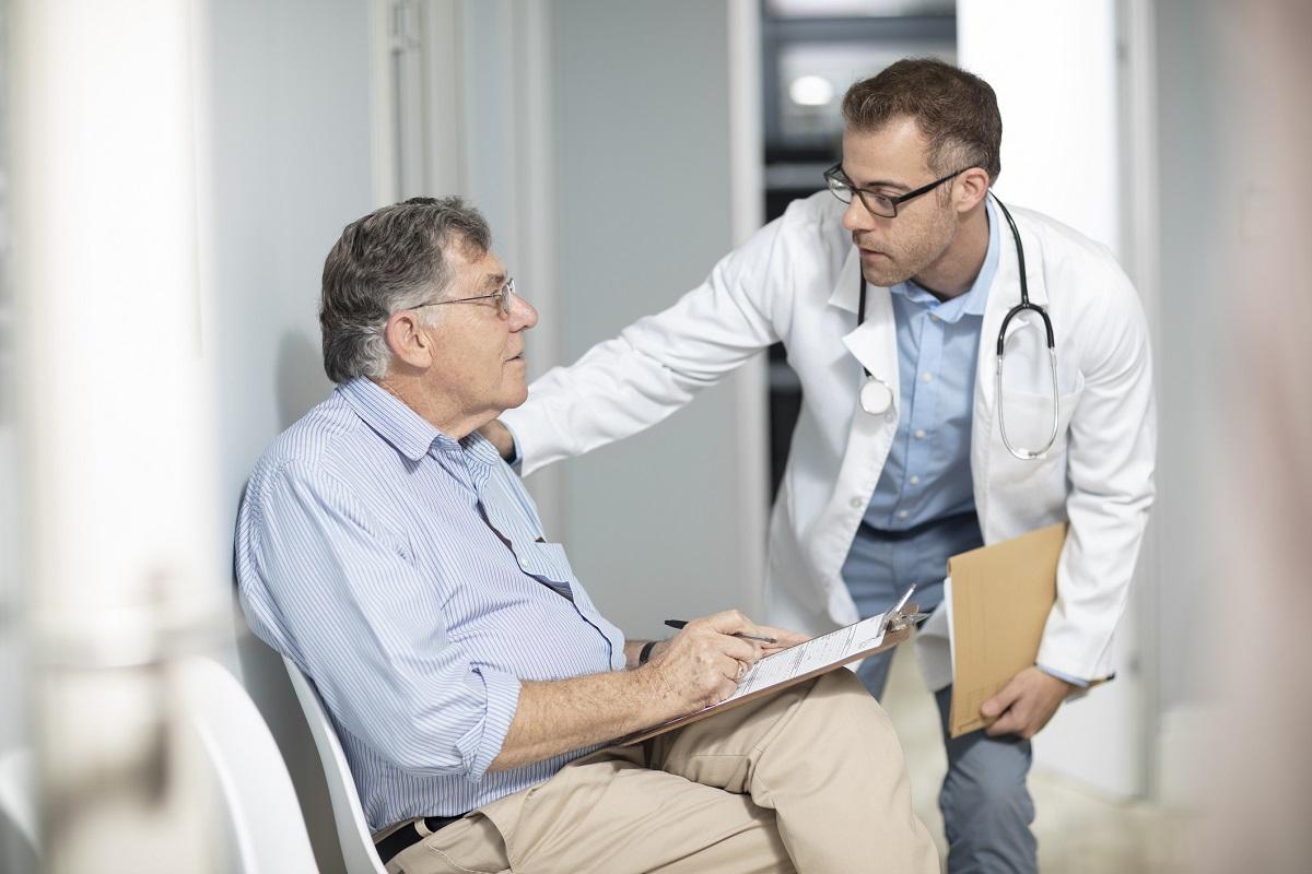 Arzt hält eine Mappe und spricht mit einem älteren Patienten im Wartebereich.