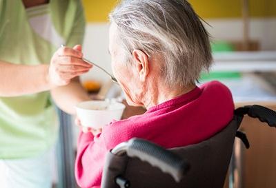 Pflegerin hilft Seniorin im Rollstuhl beim Essen.