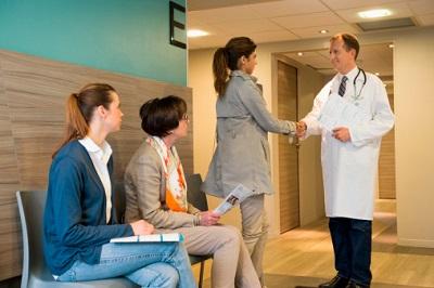 Arzt begrüßt eine Patientin, zwei weitere Patientinnen warten.