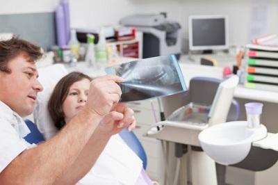 Zahnarzt zeigt Kind Röntgenbild vom Gebiss.