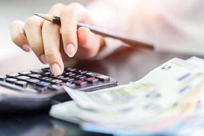 Hand mit Taschenrechner und Euro-Geldscheinen