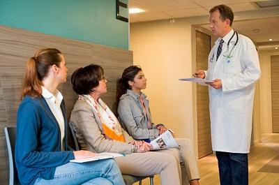 Patientinnen mit Arzt im Wartebereich einer Praxis