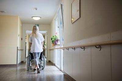 Eine Krankenschwester schiebt einen Rollstuhl durch einen Flur.