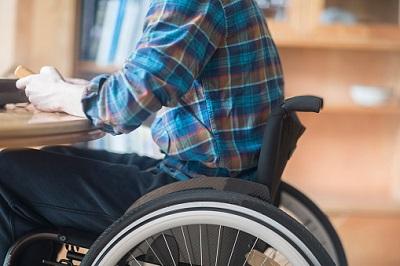 Mann im Rollstuhl sitzt am Tisch
