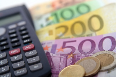Ein Taschenrechner liegt neben Euroscheinen und Münzen.