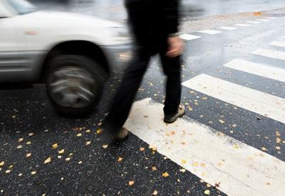 Fußgänger überquert Straße als ein Auto kommt