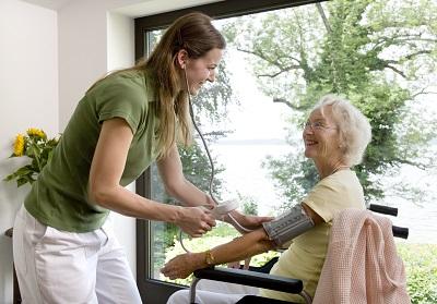 Pflegerin kümmert sich um Seniorin im Rollstuhl.