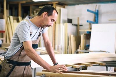 Handwerker schaut in seiner Werkstatt auf ein Touchpad.