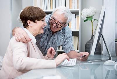 Älteres Paar sitzt vor einem Rechner mit Kreditkarte.