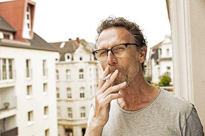 Rauchender Mann steht auf einem Balkon.