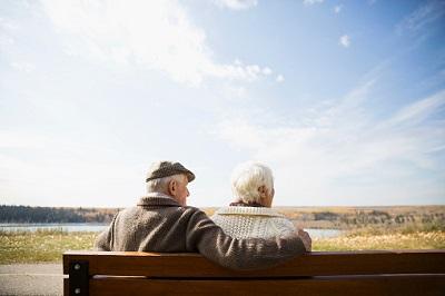 Senioren sitzen auf einer Bank und blicken in die Ferne.
